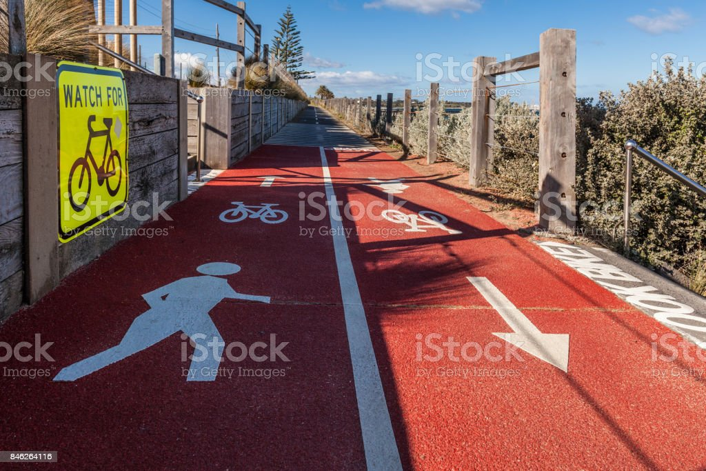Watch for bicycles and pedestrian signs on shared empty footpath vanishing in the distance on bright sunny day stock photo