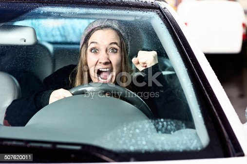 1138361116 istock photo Watch out! Enraged woman driver shakes her fist 507620011