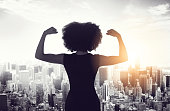 Rearview shot of an unrecognizable businesswoman standing and flexing her biceps while looking out of her high-rise office