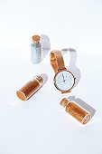 istock Watch, sequins bottles in whitespace. New Year, holiday, Christmas concept. Minimalism, Still life art 1284976394