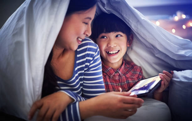 Watch this part! Cropped shot of an attractive young woman and her daughter using a digital tablet while lying under the covers vietnamese ethnicity stock pictures, royalty-free photos & images