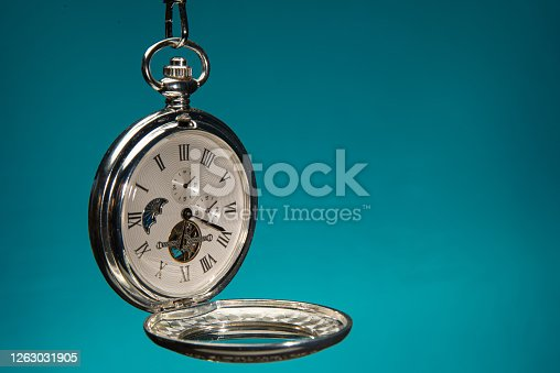 Antique victorian pocket watch on grey surface.