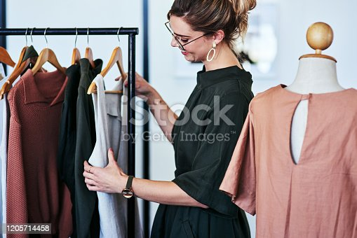 Cropped shot of a designer looking at garments on a railing in her workshop