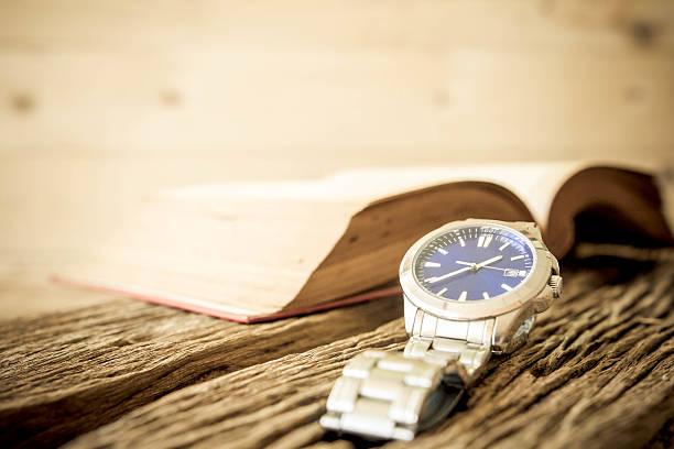 sie mit offenen buch auf alten holztisch, vintage-stil. - automatik armbanduhr stock-fotos und bilder