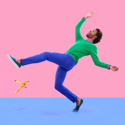 Humorous shot of a young man slipping on a banana peel agains a colorful studio background