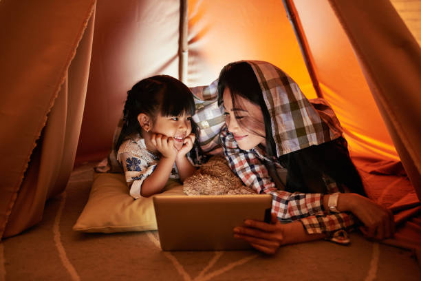 Watchinf cartoons online Pretty mother and daughter watching cartoons on digital tablet vietnamese ethnicity stock pictures, royalty-free photos & images