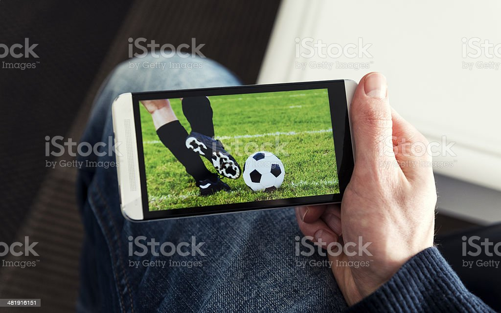 Watching a football match live streamed on mobile phone stock photo