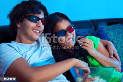 A young couple watching a 3D movie at the comfort of their home.
