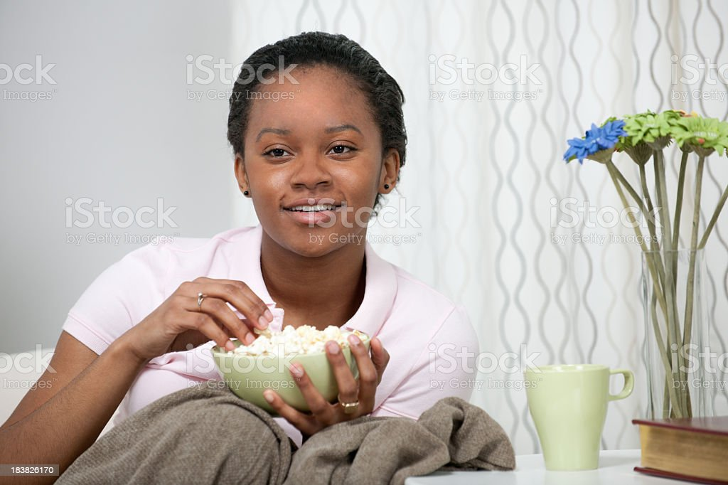 Watching a movie A young African American woman watching television and eating popcorn.  . 20-24 Years Stock Photo