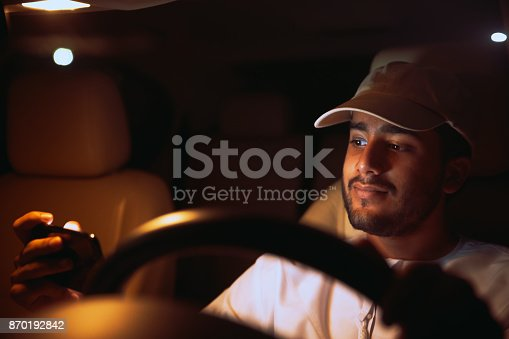 527894422istockphoto Watching a video on a smart phone while driving. 870192842