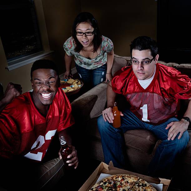 watching american football on tv - young adult friends - football friends tv night stockfoto's en -beelden