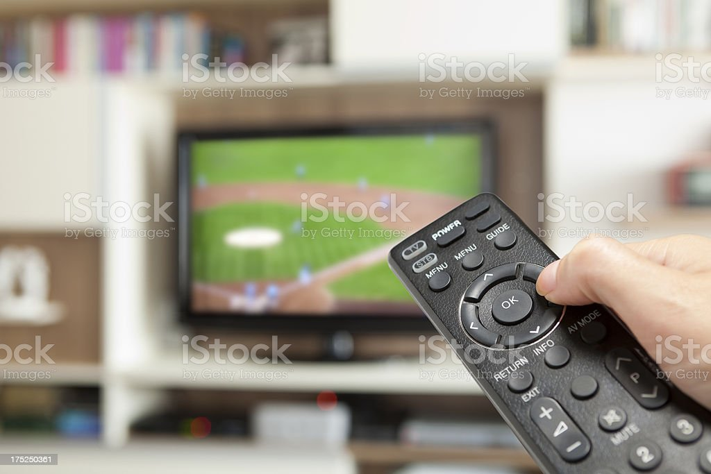 watching baseball with TV remote control in hand stock photo