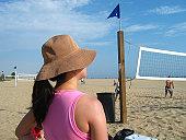 A girl watches a game of beach volleyball near Santa Monica Beach in California.