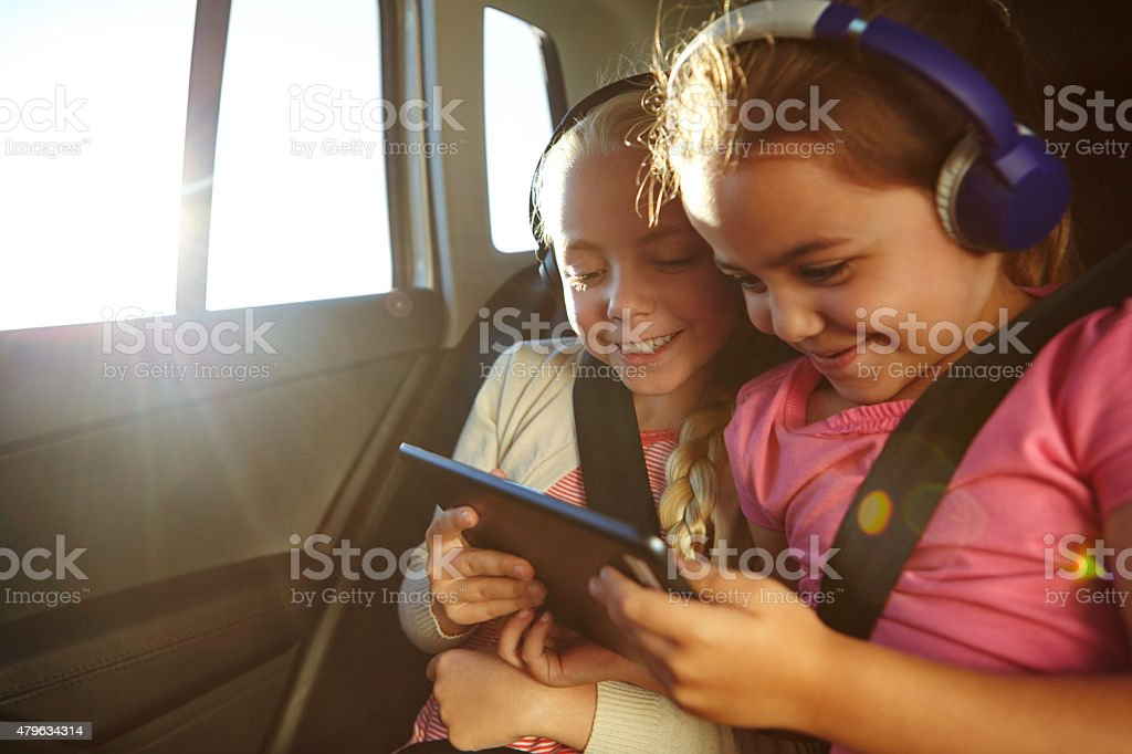 Watching cartoons on their car trip stock photo