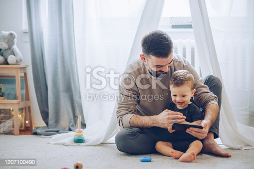 Father and son sitting on floor and watching favorite cartoon on mobile phone