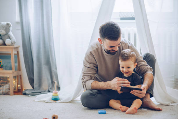 Watching cartoons together Father and son sitting on floor and watching favorite cartoon on mobile phone father stock pictures, royalty-free photos & images