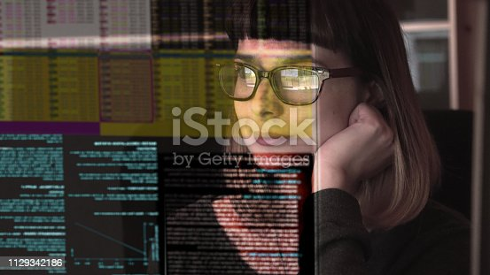 Stock photograph of a pretty young woman concentrating on a see through screen carrying a variety of data.