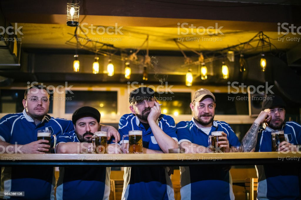 Goup of sport fans watching a football game at the pub and drinking...