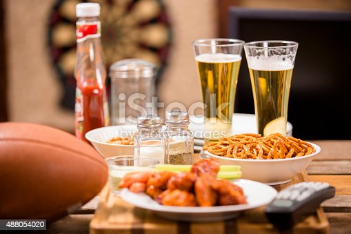 Hot wings and football in foreground.  Beer in mugs in background with blank television.  Watching the football game on TV in a local pub or sports bar.  Dartboard in background.  Bar top. Superbowl party!