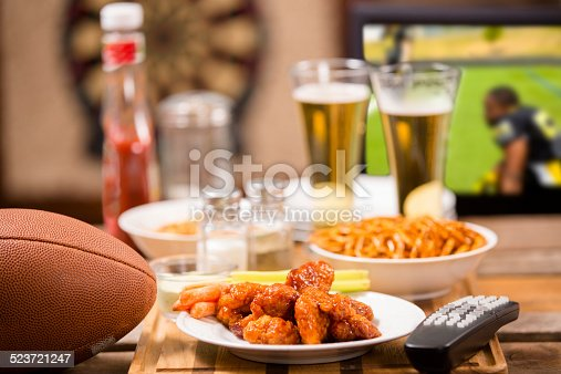 Hot wings and football in foreground.  Beer in mugs in background with television.  Football game on TV in a local pub or sports bar.  Dartboard in background.  Bar top. Superbowl party!