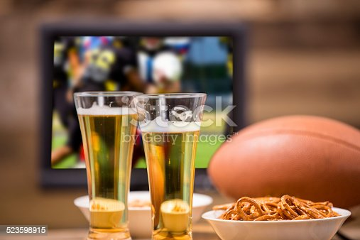 Watching the american football game at home or at a sports bar/pub. Football, beer, pretzel and peanut snacks on bar. Superbowl party!