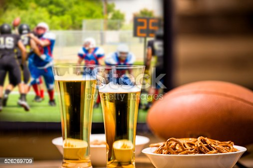 Watching the american football game at home or at a sports bar/pub on TV. Football, beer, pretzels and peanut snacks on bar or coffee table. Superbowl party!