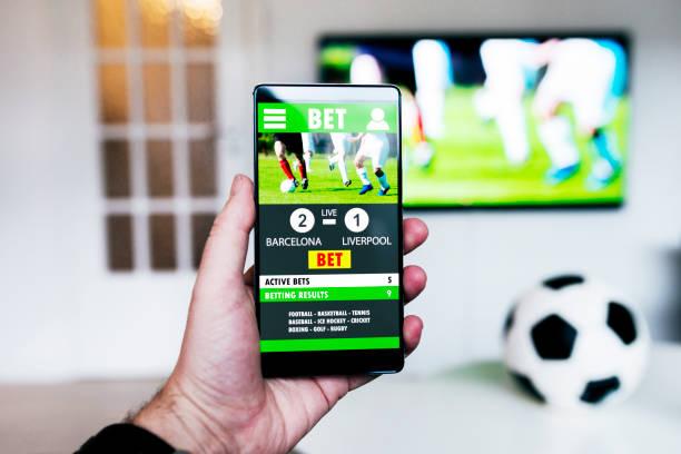 Regarder le football match à la télévision et de parier sur le jeu avec le téléphone intelligent - Photo