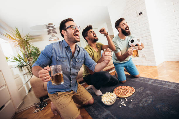Watching Football Nice happy men supporting their football team man cave stock pictures, royalty-free photos & images