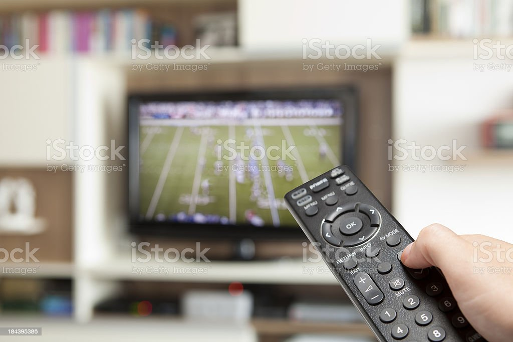 watching football with TV remote control in hand stock photo