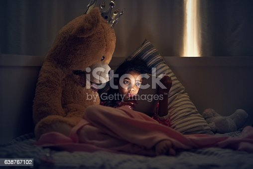 Shot of a little girl using a digital tablet while lying in bed with her teddy at night