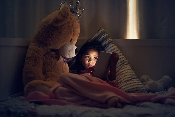 Watching her favourite cartoons before bed Shot of a little girl using a digital tablet while lying in bed with her teddy at night teddy bear stock pictures, royalty-free photos & images