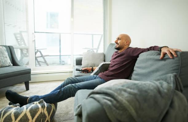watching his favourite tv show - divano procrastinazione foto e immagini stock