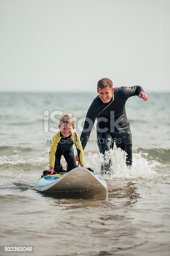 istock Watching his Son Learn how to Surf 932363046