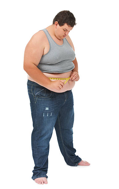 Watching his weight An obese young man measuring his waist with a measuring tap against a white background men in tight jeans stock pictures, royalty-free photos & images