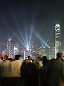 A crowd watch the weekly light show featuring famous buildings on Hong Kong island.