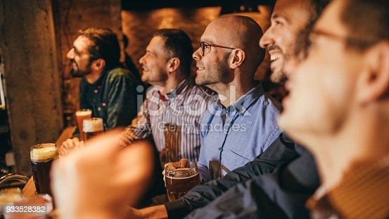 933516938 istock photo Watching match in a pub 933528382