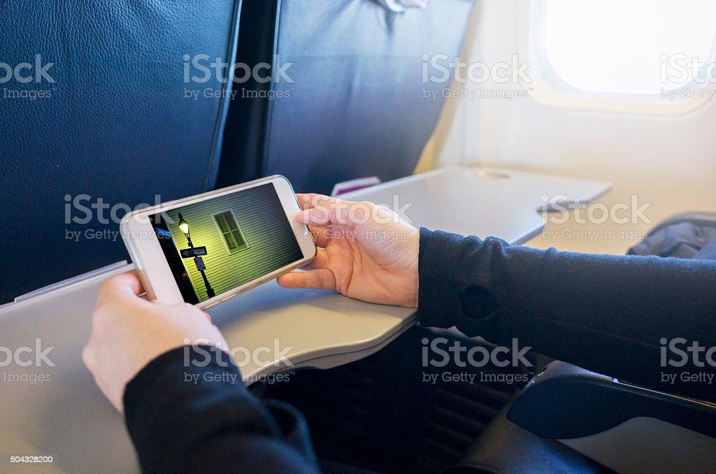 Watching Movie on Smartphone in Passenger Jet Airplane stock photo