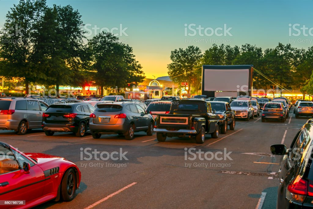 Watching movies in the open air in a car park in the city in warm...