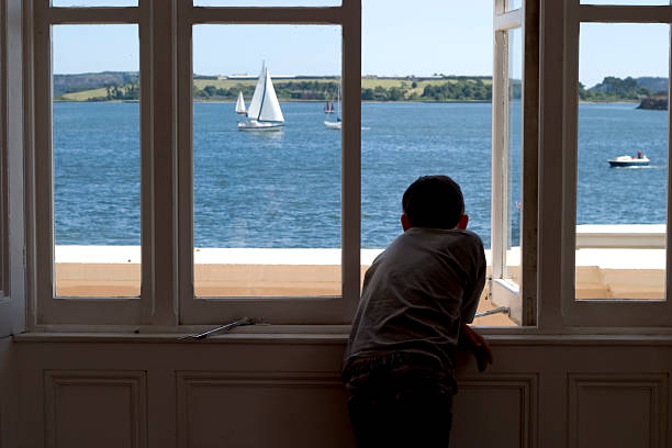 Watching Boy in silhouette looks out over Cobh harbour, Ireland boy looking out window stock pictures, royalty-free photos & images