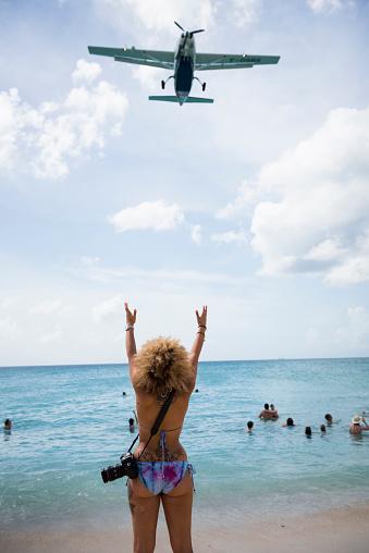 A woman visiting St. Maarten's famous Maho Beach reaches toward a Cessna 208B Grand Caravan as it comes in for landing at Princess Juliana International Airport. (November 2015)