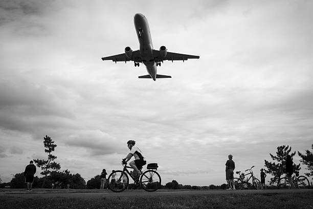 Watching planes land at Reagan National Airport Arlington, Virginia, USA - July 3, 2016: At Gravelly Point in Arlington, Virginia, an American Eagle jet passes over cyclists and other people moments before touching down at Ronald Reagan Washington National Airport. ronald reagan washington national airport stock pictures, royalty-free photos & images