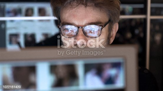 A mature man is surrounded by computer displays, he's closely watching a monitor. On the screens & reflections there are scrolling thumbnail photos and crowds of people with data; he uses a touch screen to see information surrounding these IDs.