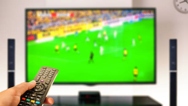 watching soccer at home tv with remote control on hand stock photo