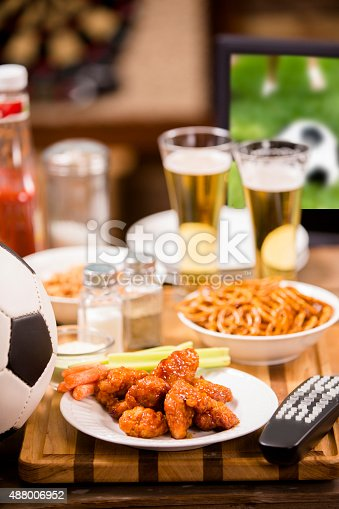 Watching the soccer game on television at a local sports bar or pub.  Soccer ball, spicy chicken wings, and TV remote in foreground.  Beer,  TV with soccer game on screen, and dartboard in background.  Wooden bar counter.  No people.