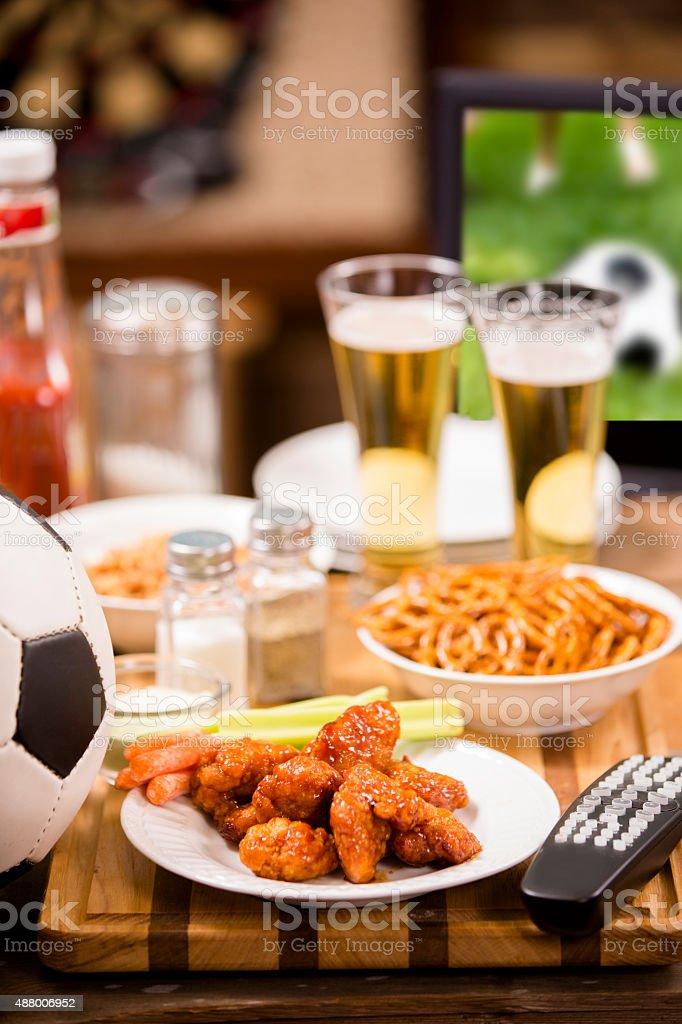 Regarder match de football à la télévision au pub local. Ailes de poulet. - Photo