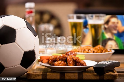 istock Watching soccer game on television at local pub. Chicken wings. 524325849