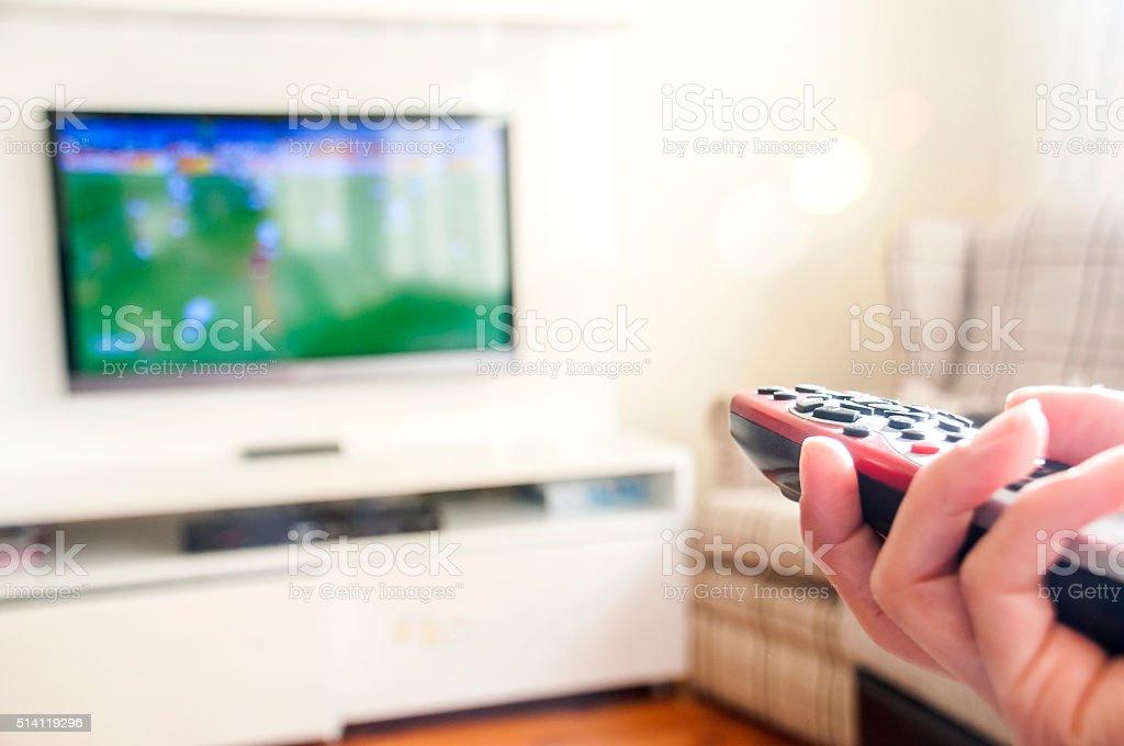 Vor Fußball auf einem intelligente TV-Fernbedienung in der Hand – Foto