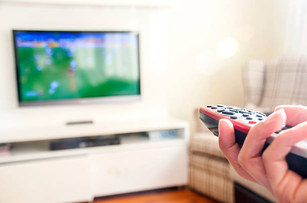 Watching soccer on a smart TV remote control in hand Smart TV also enjoy football cable tv stock pictures, royalty-free photos & images