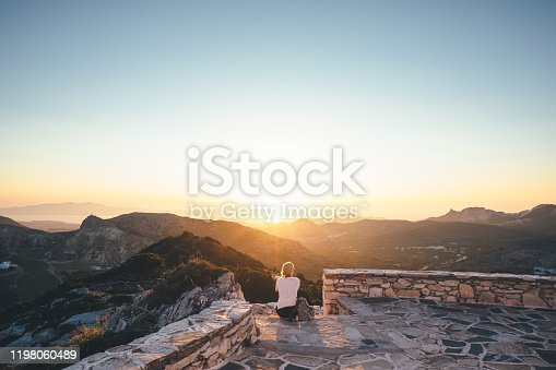 Young woman enjoying the sunset from the church on top of the hill (Naxos, Greece).