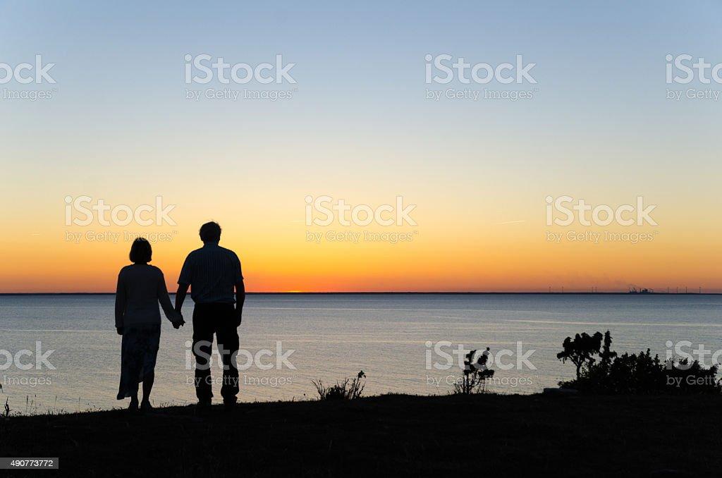 Watching sunset hand in hand stock photo